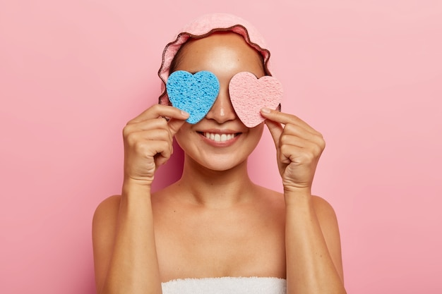 Positive ethnic woman covers eyes with two sponges, has beauty treatments, smiles happily, wears shower cap on head, has healthy skin, isolated on pink wall. purification, face care concept