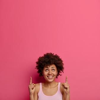 La donna etnica positiva punta il dito verso lo spazio della copia sopra la testa per la tua pubblicità, attira l'attenzione su una grande offerta, sorride felice, isolata sul muro rosa, dà consigli, promuove il prodotto