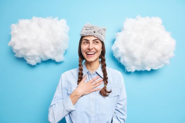 긍정적 인 유럽 여성 모델은 가슴에 손을 잡고 행복하게 미소를 지으며 파란색에 수면 마스크와 셔츠 포즈를 입었습니다.