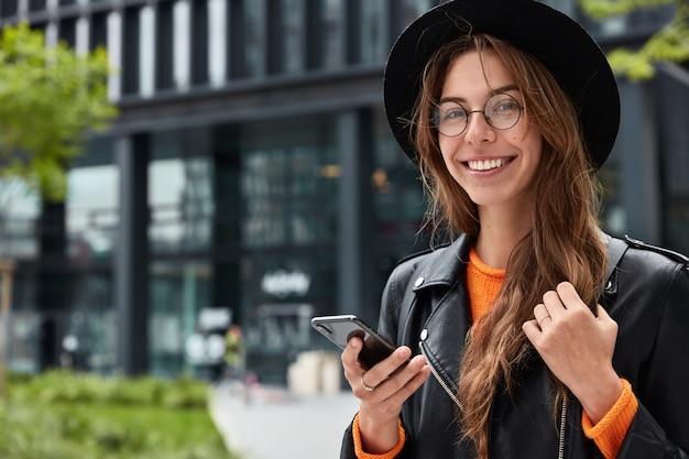 La donna europea positiva utilizza la moderna applicazione del telefono cellulare per passeggiare nel centro, indossa abiti alla moda