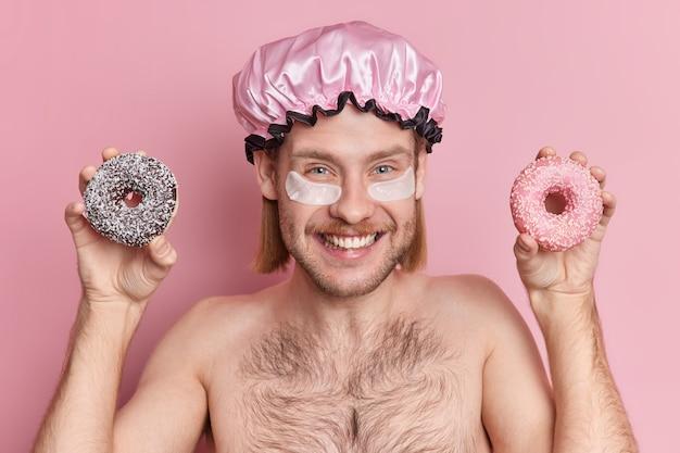 Un ragazzo europeo positivo con un'espressione felice applica cerotti di collagene sotto gli occhi, tiene dolci ciambelle, indossa la cuffia per la doccia e sta mezzo nudo
