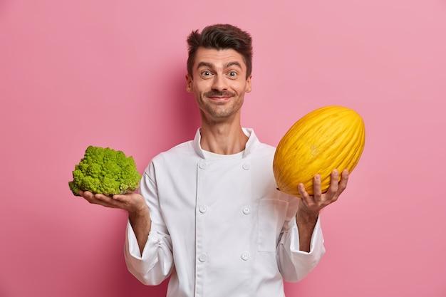 ポジティブなヨーロッパ人男性シェフがサラダを準備し、大きなメロンとブロッコリーを持っています