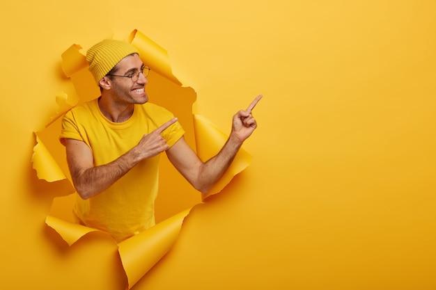 ポジティブなヨーロッパ人男性モデルは両方の人差し指で右を指し、提案者は製品を使おうとし、脇を向いています