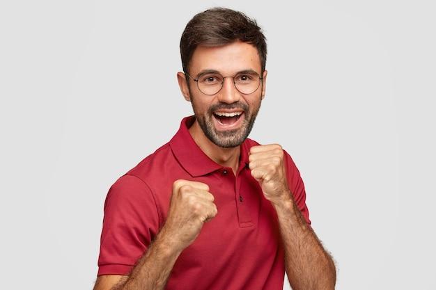 Позитивный европейский мужчина поднимает сжатые кулаки, готовый нанести удар или драться, широко улыбается, одет в повседневную красную футболку, защищается изолированно за белой стеной. энергичные жесты человека рад