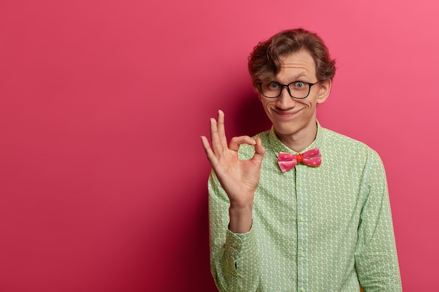 Positive european man shows okay gesture with fingers, says good job, excellent, well done, got everything under control, wears formal outfit, makes confirmation sign, isolated on pink wall free space