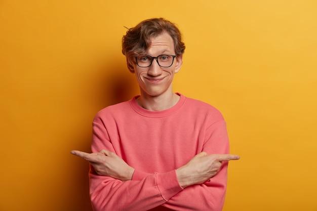 Uomo europeo positivo con sguardo esitante, incrocia le braccia sul corpo, indica di lato, sceglie tra due oggetti, indossa occhiali e maglione. è ora di fare una scelta. il maschio ha bisogno di consigli su cosa scegliere