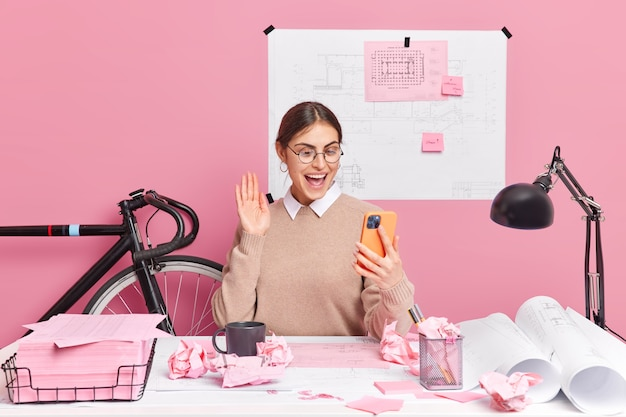 ポジティブなヨーロッパの女性がビデオ通話の波を手のひらにし、最新のスマートフォンの作品をレポートに保持し、デスクトップでホームタスクのポーズを準備します