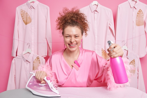 Positive european woman with curly hair smiles broadly dressed in robe holds steam iron and water spray bottle being in good mood poses against burned ironed clothes behind. housework concept
