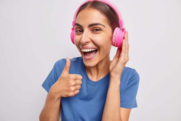Positive european woman with dark hair keeps thumb up shows like gesture enjoys playlist wears wireless headphones casual blue t shirt agrees with you stands over grey wall