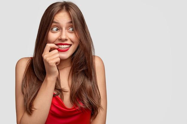 不思議な幸せな表情でポジティブなヨーロッパの女性、人差し指を口の近くに保つ