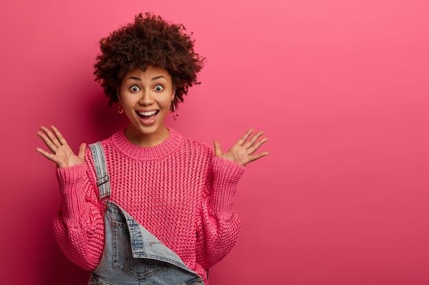 ポジティブに興奮したアフリカ系アメリカ人女性が喜びで手のひらを上げる