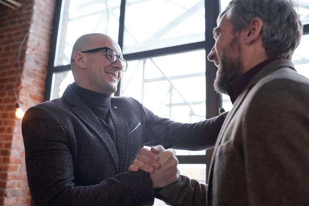 Позитивно взволнованные друзья-мужчины пожимают друг другу руки, радуясь видеть друг друга в кафе-лофте