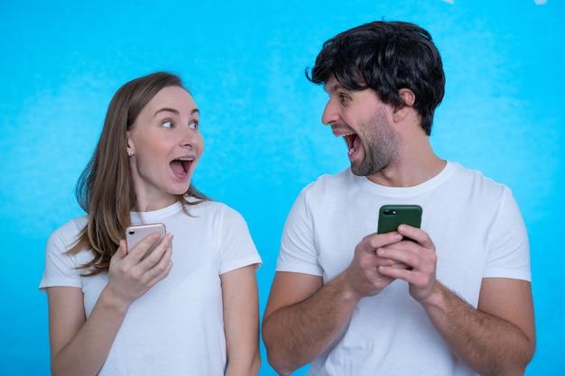 Позитивно возбужденные мужчина и женщина кричат и смотрят друг на друга, используя мобильные телефоны