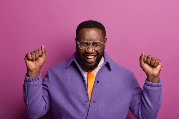 긍정적 인 흥분된 남자가 주먹을 들고, 승리를 축하하고, 승리를 기뻐하며, 긍정적으로 웃으며, 보라색 재킷을 입고, 라일락 벽 위에 절연되어 있고, 강력 함을 느끼고, 눈을 감습니다.