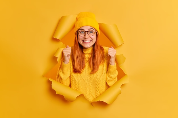 Positive excited redhead woman raises fists, wears yellow hat and knitted jumper, expresses joy, breaks through paper wall