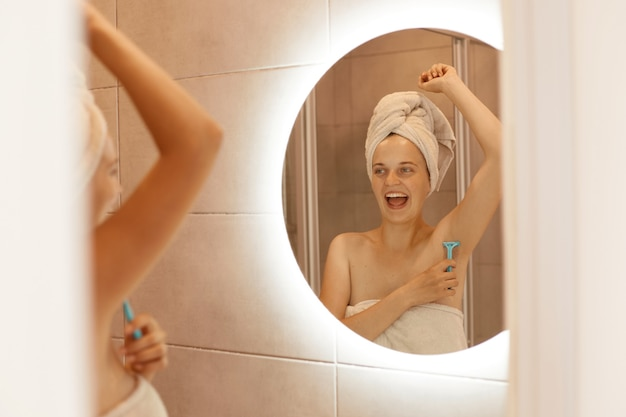 Positive excited young adult woman shaving armpit in bathroom, looking at the mirror reflection with open mouth, being wrapped in white towel, doing depilation.