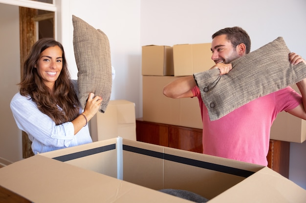 Positive excited young man and woman getting out cushions of open carton box, enjoying moving and unpacking things