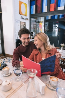 Positive exuberant couple reading menu and laughing