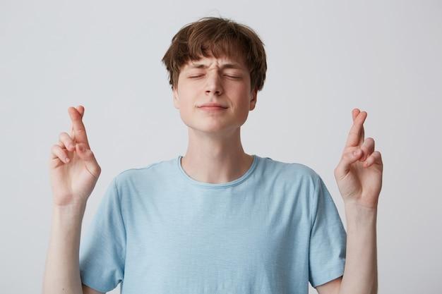 Положительный верный молодой парень, закрывающий глаза с надеждой