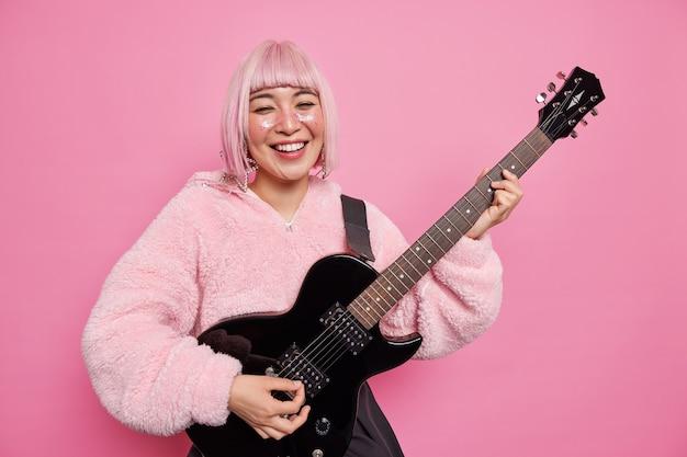 긍정적 인 유명한 록 소녀가 일렉트릭 어쿠스틱 기타를 연주하는 것은 재미를 느끼고 무대에서 공연하는 미친 척은 세련된 옷을 입습니다.