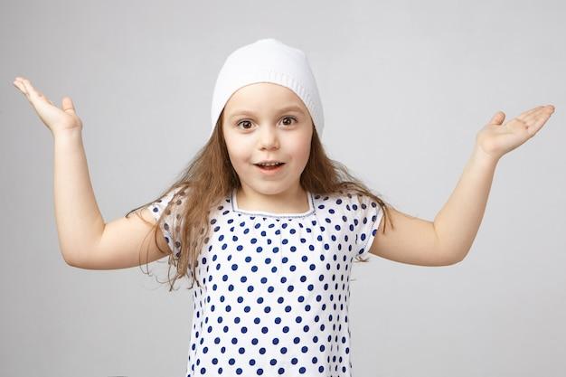 Ragazza graziosa affascinata positiva di 5 anni in cappello e maglietta che solleva le mani