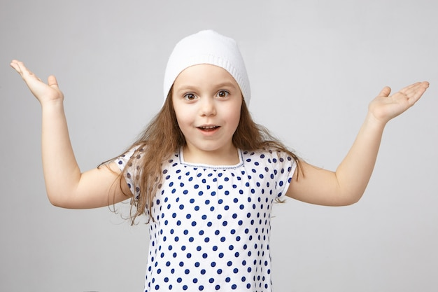 帽子とtシャツの手を上げるポジティブに魅了された5歳のかわいい女の子