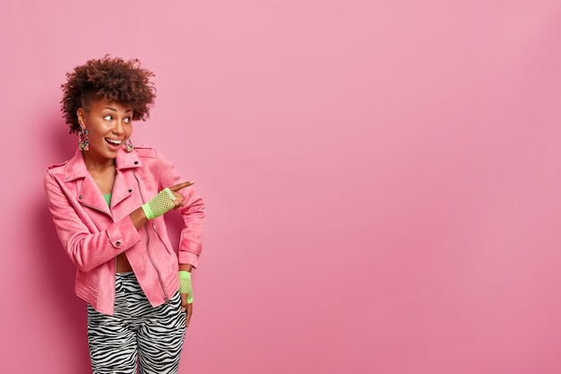 Positive fashionable curly haired woman points index finger away on blank space, shows promo banner, gives recommendation, direction to sport club, indicates awesome place