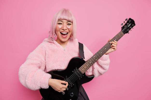 핑크색 헤어 스타일의 긍정적 인 패셔너블 한 여성 록 스타는 어쿠스틱 기타를 연주하며 스타일리쉬 한 코트를 입은 자신의 음악 밴드가 실내에서 그녀의 앨범 포즈를 위해 신곡을 만들고있다. 행복 한 세련 된 여자 기타리스트