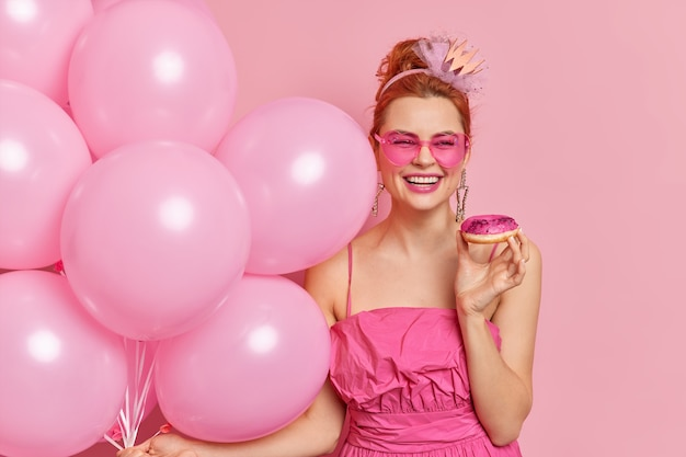 Positive fashionable redhead woman smiles broadly has festive mood holds tasty doughnut inflated balloons wears heart shaped sunglasses and dress