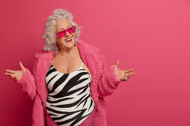Positive fashionable senior woman spreads palms is in a happy mood