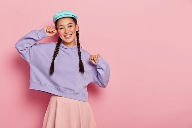 메이크업을 가진 긍정적 인 유행의 십대 소녀는 세련된 모자, 자주색 스웨터와 치마를 입고 좋은 분위기에 있으며 분홍색 벽 위에 고립 된 그룹 동료와 만나게됩니다.