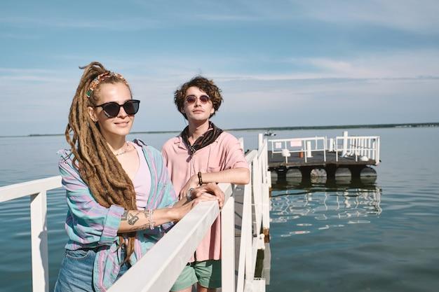 화창한 여름날 사진을 위해 포즈를 취한 호수 부두에 서 있는 긍정적인 유행 젊은이들