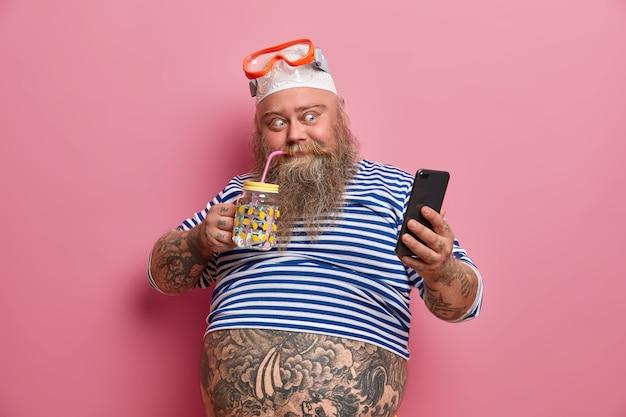 Positive fatso guy drinks fresh water, takes photo via cellphone, wears swimming snorkeling mask, undersized sailor shirt