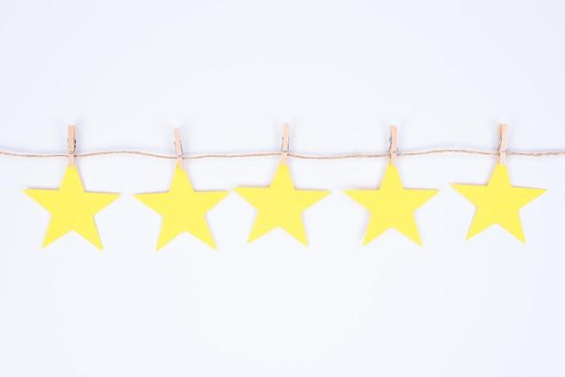 Концепция положительной обратной связи. крупным планом фото пяти маленьких золотых звезд, висящих на нитке, прикрепленных к маленьким прищепкам, изолированным на белом фоне