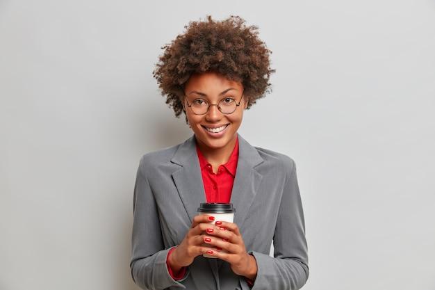 정장 차림의 긍정적 인 여성 행정 보조원, 쾌활한 표정, 사무실에서 커피 브레이크 즐기기, 일회용 음료 컵 보유