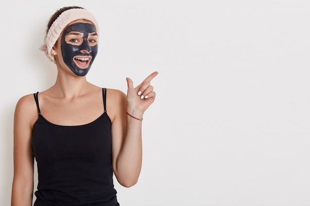Positive female applies nourishing mask on face, pointing fore finger aside on copy space, undergoes beauty treatments, poses indoor against white wall. copy space.