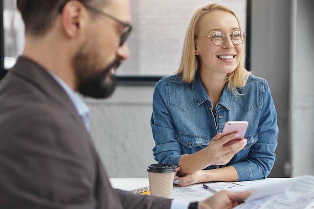 肯定的な女性アシスタントとオフィスでひげを生やした深刻な男性起業家