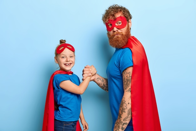 Positive female child holds hand of bearded father superhero