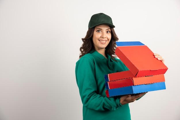 Corriere femminile positivo che tiene la scatola della pizza aperta.