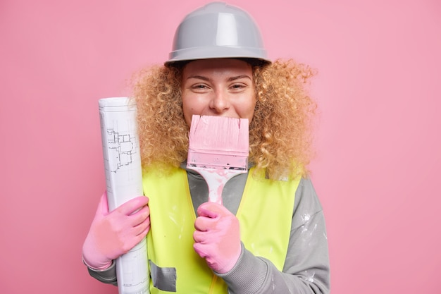 Positive female engineer with curly bushy hair keeps paint brush over mouth holds blueprint wears protective helmet reflecting jacket has fun at construction site. building inspector indoor.