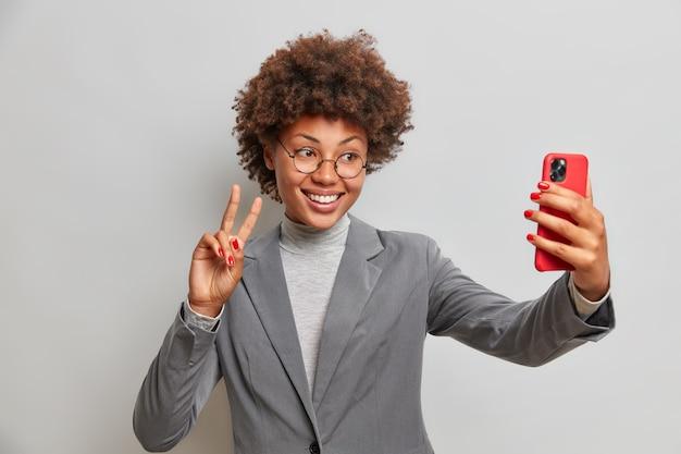 Позитивная женщина-предприниматель делает жест мира, делает селфи через смартфон, наслаждается видеоконференцией с коллегой, носит серую официальную одежду, позирует в помещении