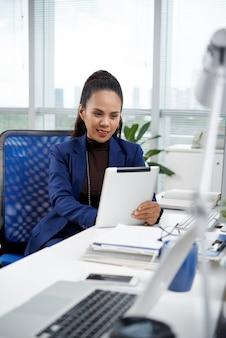 タブレットコンピューターで彼女の同僚の肯定的な女性起業家の読書レポート