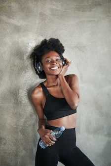 Positive female feels satisfied. portrait of african american girl in fitness clothes having a break after workout