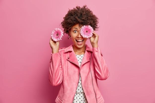 ポジティブな女性の花屋が香りのよいガーベラの花で目を覆い、特別な日のための花束を作ります笑顔はピンクの壁に隔離されたファッショナブルなジャケットを広く着ています