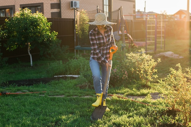 ポジティブな女性の庭師は、晴れた暖かい春の日にシャベルでベッドを掘ります。新しい季節のための植物の手入れと植え付けの概念