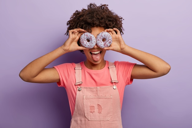 La femmina positiva tiene due ciambelle viola sugli occhi, tira fuori la lingua, indossa una maglietta rosa e una salopette, essendo golosa, si diverte, posa al coperto sopra il muro viola. mangia gustosi dessert con me