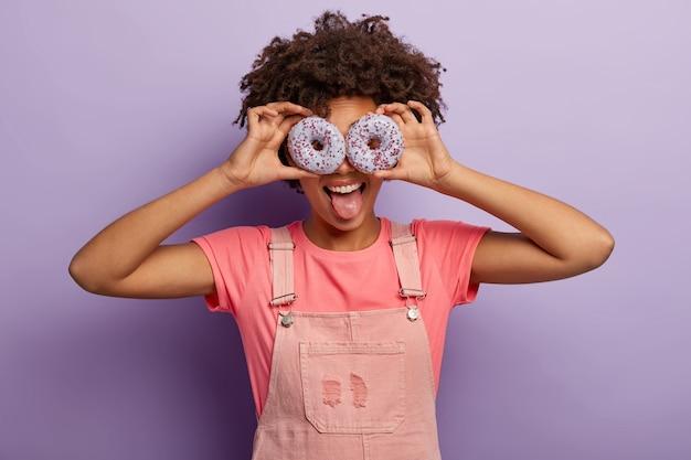 ポジティブな女性は、目に2つの紫色のドーナツを持ち、舌を突き出し、ピンクのtシャツとダンガリーを着て、甘い歯で、楽しんで、紫色の壁の上で屋内でポーズをとります。私と一緒においしいデザートを食べてください