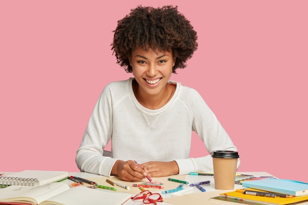 Positive female illustrator makes sketches with crayon on blank sheet of paper