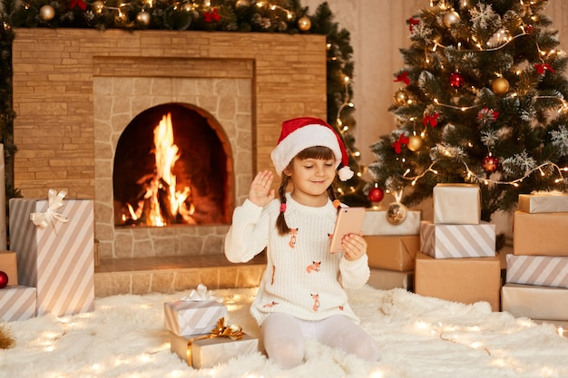 Positive female kid wearing white sweater and santa claus hat, sitting on floor near christmas tree, present boxes and fireplace, waving hand to her friends while talking with them via video call.