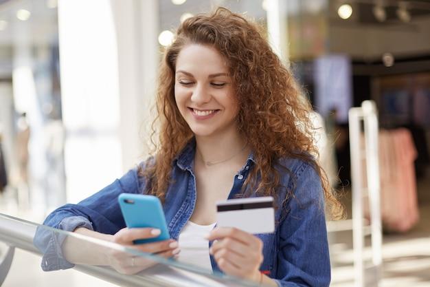 肯定的な女性モデルはスマートフォンでクレジットカードの番号をダイヤルし、彼女の銀行口座を確認し、買い物をし、購入の支払いにいくらかのお金が必要です。人、支払い、技術、購入コンセプト